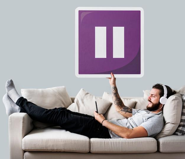 Mann auf einer couch, die eine pausenknopfikone hält