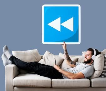 Mann auf einer Couch, die eine Rückspulenknopfikone hält
