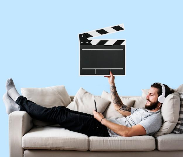 Mann auf einer couch, die eine scharnierventilikone hält