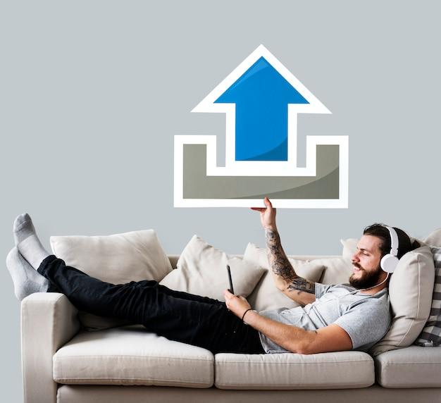 Mann auf einer couch, die eine upload-ikone hält