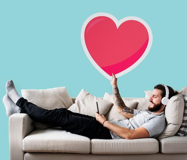 Mann auf einer couch, die einen herz emoticon hält