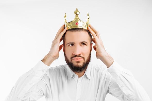 Mann auf einer weißen wand trägt eine krone auf seinem kopf,