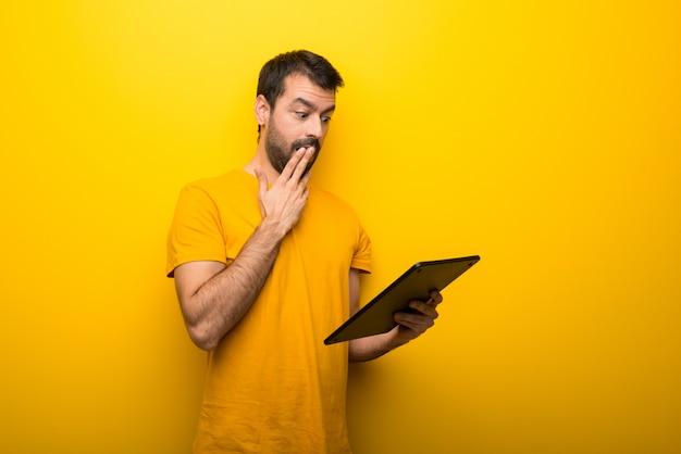 Mann auf getrennter vibrierender gelber farbe mit einer tablette