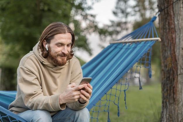 Mann auf hängematte, die musik auf ohrhörern mit smartphone hört