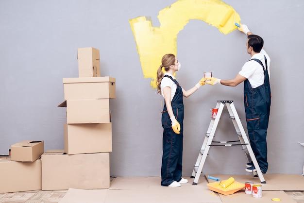 Mann auf labber und frau in uniform paint grey wall