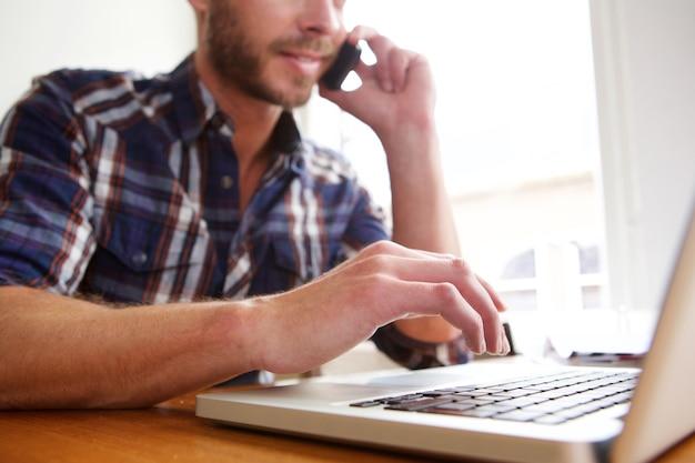 Mann auf laptop-computer und unterhaltung am telefon