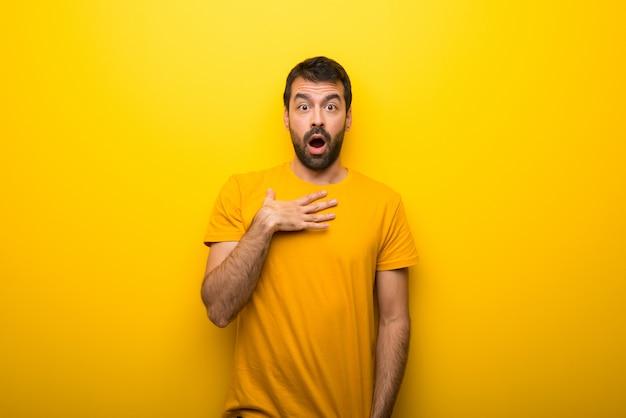 Mann auf lokalisierter vibrierender gelber farbe beim schauen überrascht und entsetzt