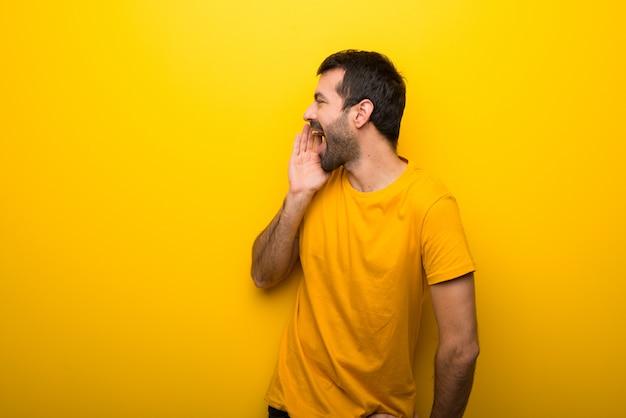 Mann auf lokalisierter vibrierender gelber farbe, die mit dem mund weit offen zum seitlichen schreit