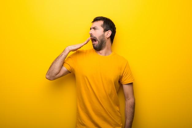 Mann auf lokalisierter vibrierender gelber farbe, die weit offenen mund mit der hand gähnt und bedeckt