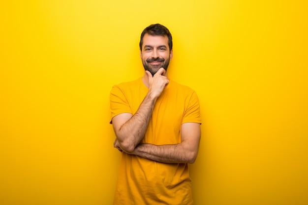 Mann auf lokalisierter vibrierender gelber farbe, die zur front mit überzeugtem gesicht lächelt und schaut