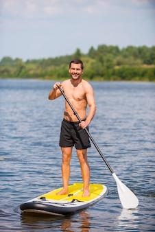 Mann auf paddleboard. hübscher junger mann, der auf seinem paddleboard surft und lächelt