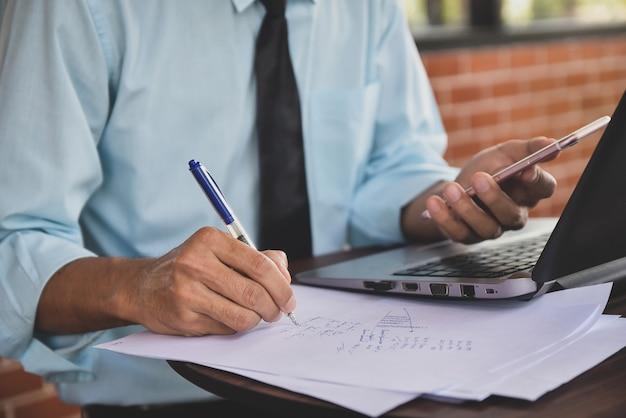 Mann auf papieren schreiben und mit dem smartphone