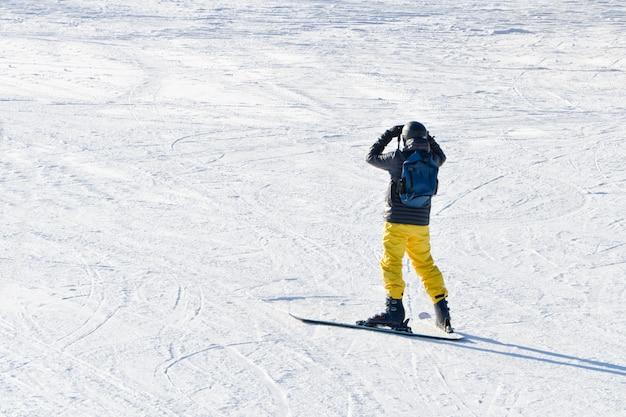 Mann auf skiern sieht aus der ferne. blick von hinten