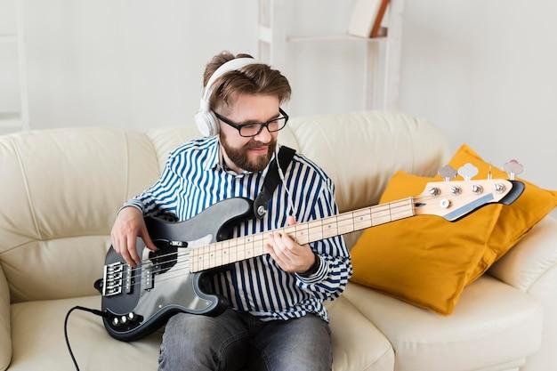Mann auf sofa mit e-gitarre