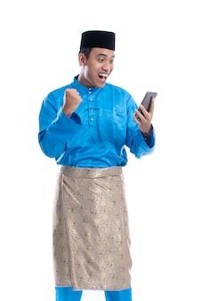 Mann aufgeregt, während er auf sein telefon schaut