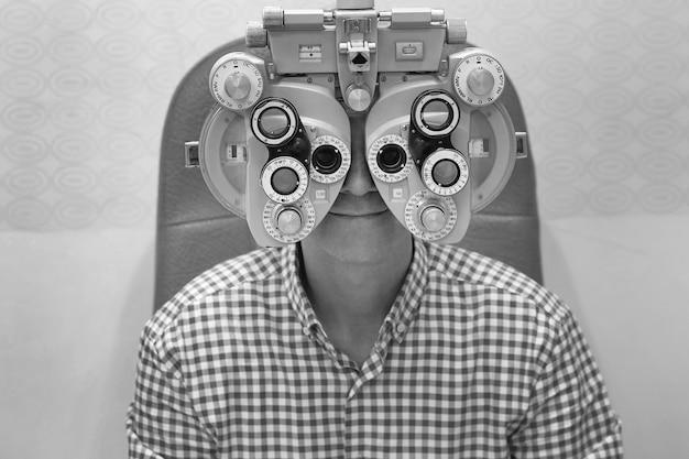 Mann augenarzt untersucht geduldigen mann mit augenoptiker-testrahmen. männlicher patient zur überprüfung des sehvermögens in der augenklinik
