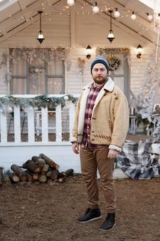 Mann außerhalb des hauses im winter zu weihnachten