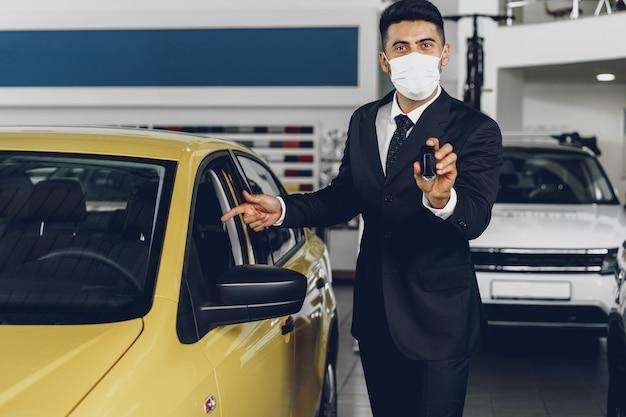 Mann autohändler, der medizinische maske auf seinem arbeitsplatz trägt