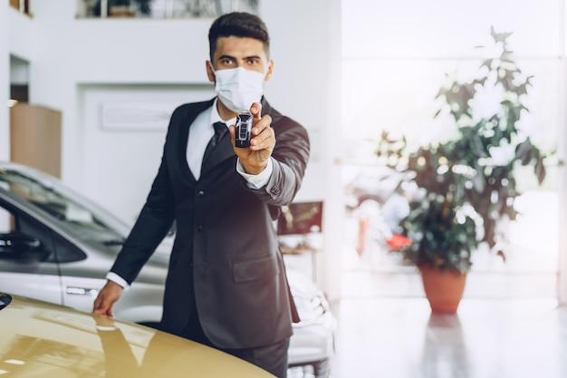 Mann autohändler, der medizinische schutzmaske an seinem arbeitsplatz trägt