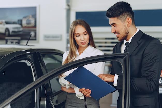Mann autohändler zeigt einer frau käufer ein neues auto