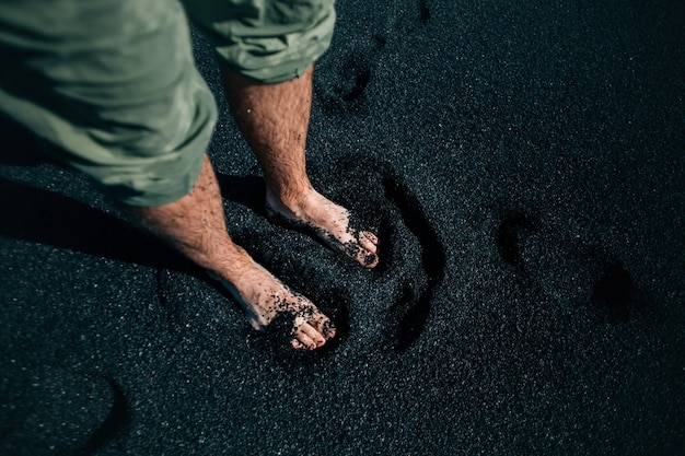 Mann barfuß auf schwarzem sandstrand in island