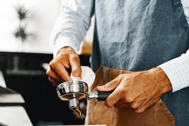 Mann barista bereitet kaffee auf professioneller kaffeemaschine zu