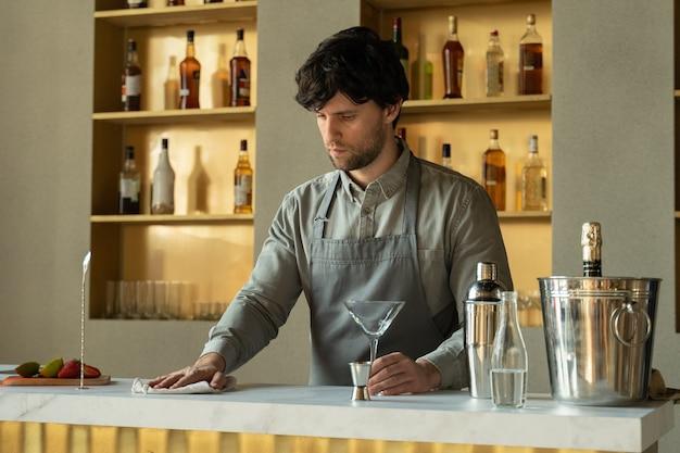 Mann-barkeeper, der an der bartheke steht, die tisch fröhlichen barkeeper am arbeitsplatz abwischt