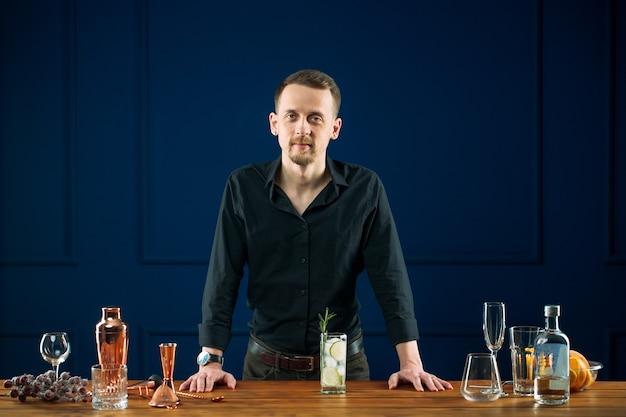 Mann barkeeper, der hinter schreibtisch mit gin tonic steht