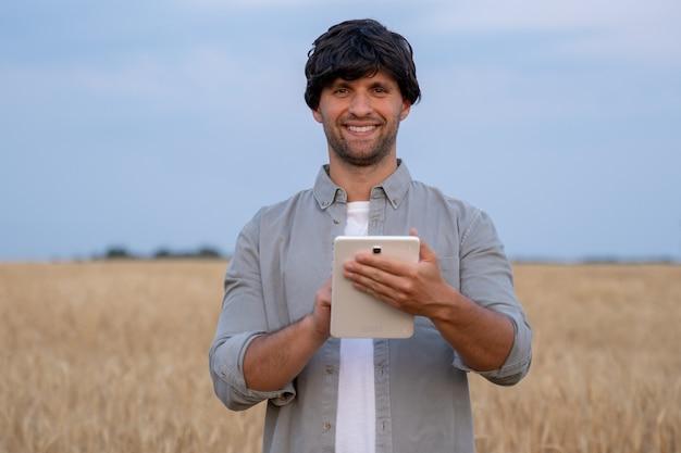 Mann bauer mit digitalem tablet-computer auf einem weizenfeld stehen und apps verwenden und quali...