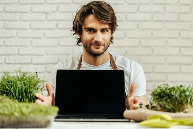 Mann bauer zeigt schwarzen bildschirm des laptops und sitzt mit sprossen am tisch