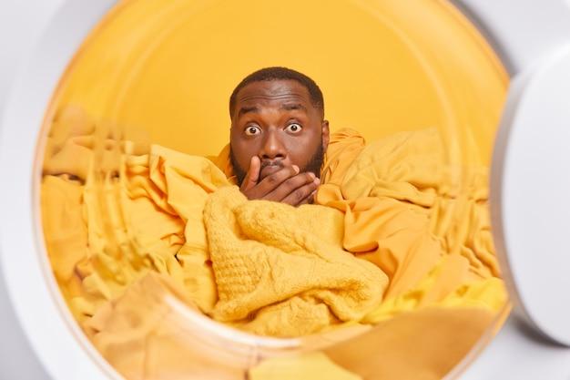 Mann bedeckt den mund mit der hand, die mit gelber wäsche bedeckt ist, hat verwanzte augen und findet etwas sehr schockierendes heraus