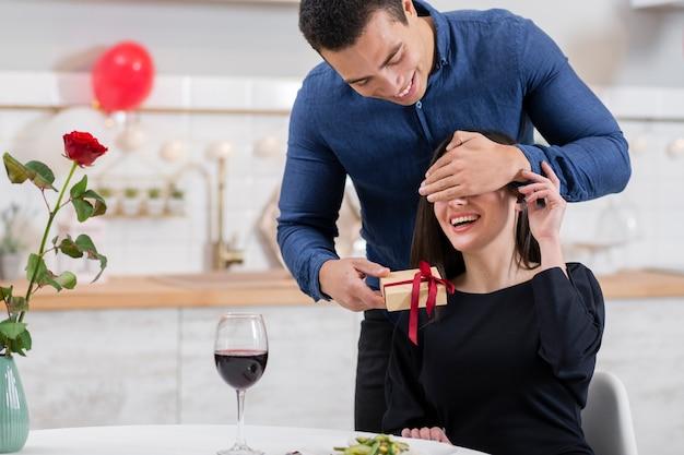 Mann bedeckt die augen seiner freundin, bevor er ihr ein geschenk gibt