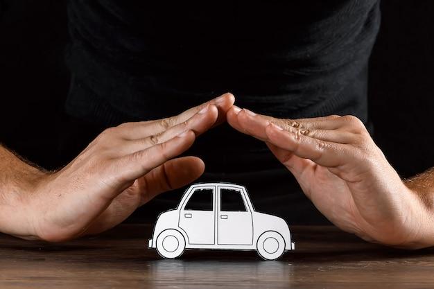 Mann bedeckt ein papierauto mit seinen händen