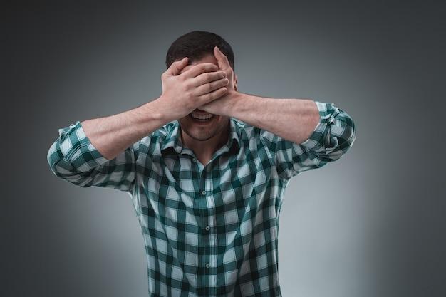 Mann bedeckt seine augen mit der hand, freizeitkleidung. studioaufnahme.