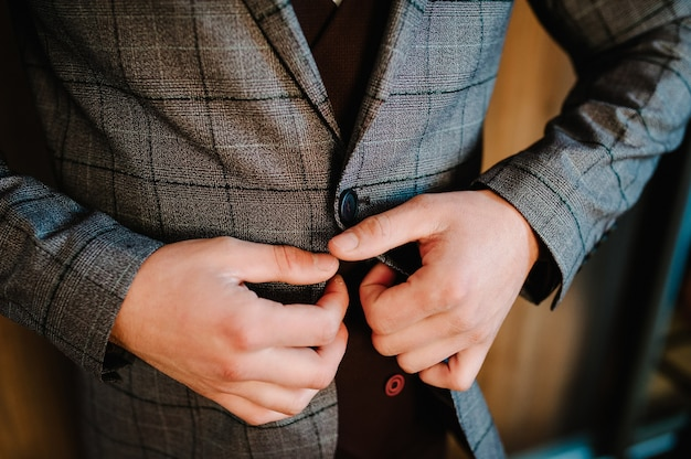 Mann befestigt die knopfjacke. der bräutigam in einem anzug, hemd steht auf raumhintergrund. nahansicht.