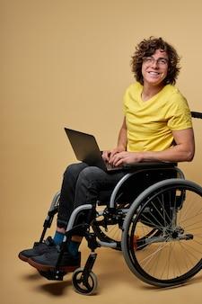 Mann behinderter student, der für prüfung mit laptop vorbereitet, sitzt auf rollstuhl isoliert im studio. porträt. online-bildung für behinderte