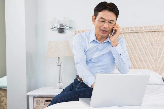 Mann bei einem telefonanruf unter verwendung des laptops im schlafzimmer