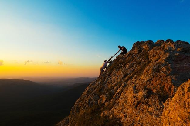 Mann beim klettern mit einem anderen mann, der hilft