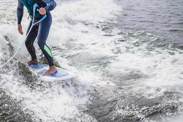 Mann beim wakesurfen. winken vom boot.