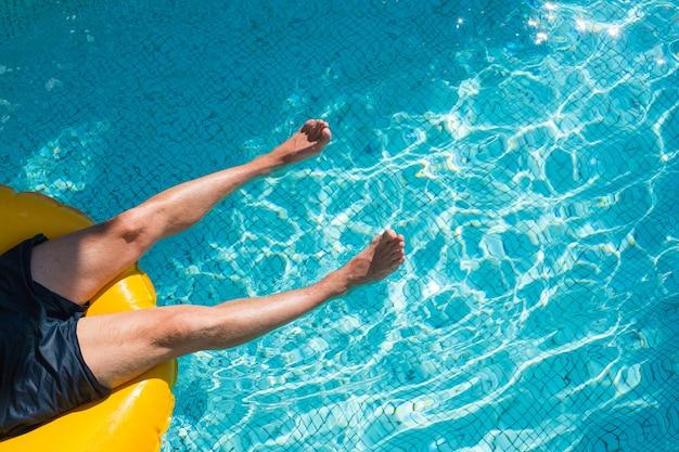 Mann beine entspannen auf pool luftmatratze schweben im pool