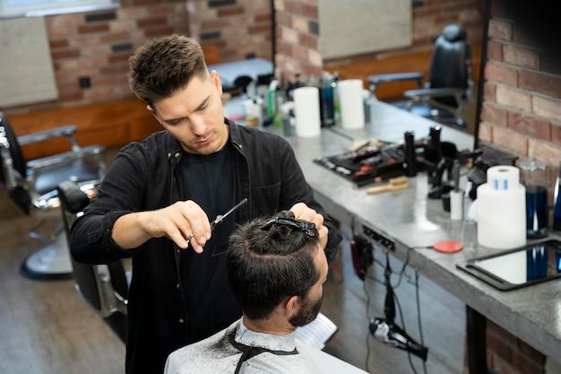 Mann bekommt einen haarschnitt im salon aus nächster nähe