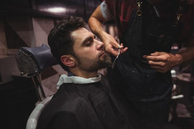 Mann bekommt seinen bart mit einer schere getrimmt