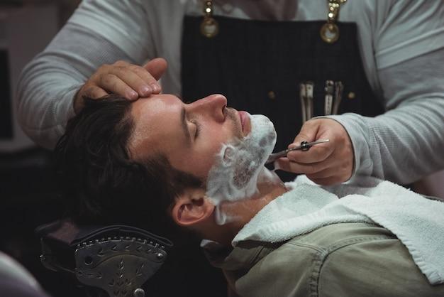 Mann bekommt seinen bart mit rasiermesser rasiert