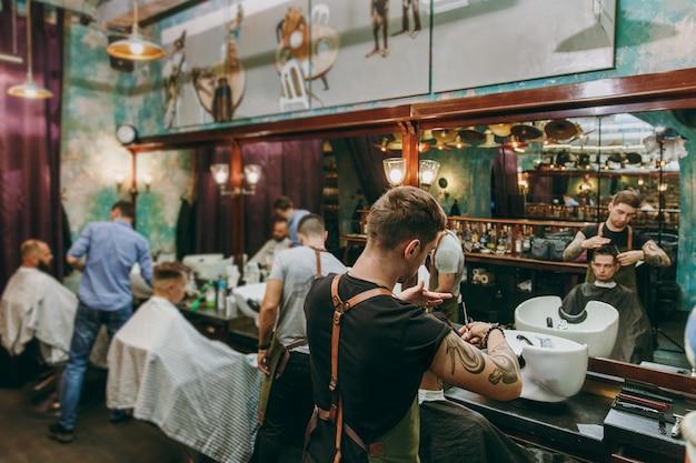 Mann bekommt trendigen haarschnitt im friseurladen. der männliche friseur in tätowierungen, der dem kunden dient.