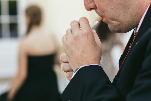 Mann beleuchtet die zigarre, die es vom wind versteckt