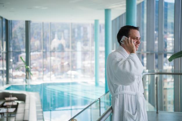 Mann benutzen das handy im luxushotel spa in der nähe des pools
