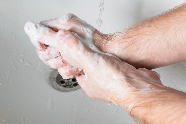 Mann benutzen seife und hände waschen unter dem wasserhahn. hygienekonzept hand detail.