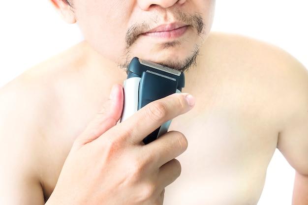 Mann benutzt den rasierapparat, der über weißem hintergrund lokalisiert wird