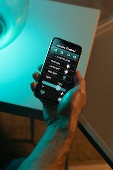 Mann benutzt ein smartphone in seinem automatisierten zuhause
