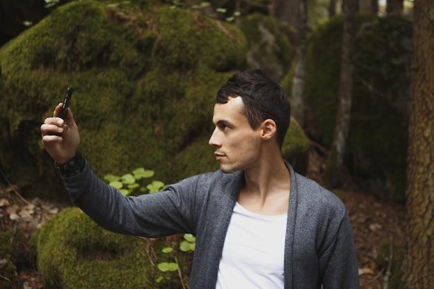 Mann benutzt handy, unscharfes bild von touristen, die im wald als hintergrund spazieren.